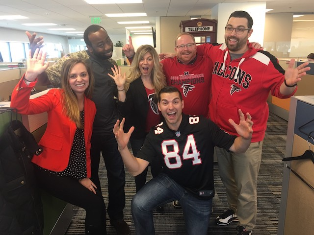 Slide Show Image #3: Group of CareerBuilder employees in the office, waving to camera and wearing sports jerseys