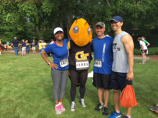 Slide Show Image #4: Four CareerBuilder employees after a marathon, wearing their race numbers and standing next to the Georgia Tech mascot